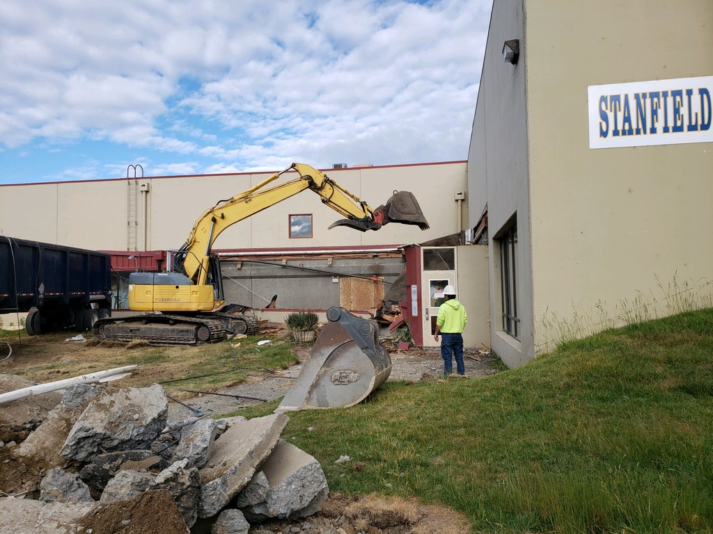 Demolition of front of building with big machinery