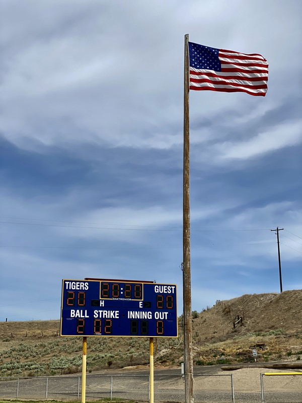 American flag in front of football scoreboard reading 2020